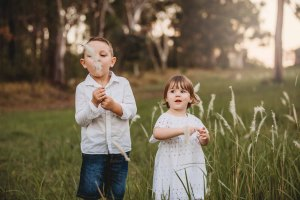 A brother and sister standing in long grass