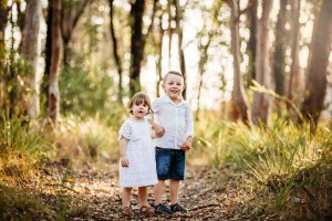 Siblings holding hands in the sunlit bushland