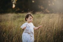 A little girl carefully walking through long grass