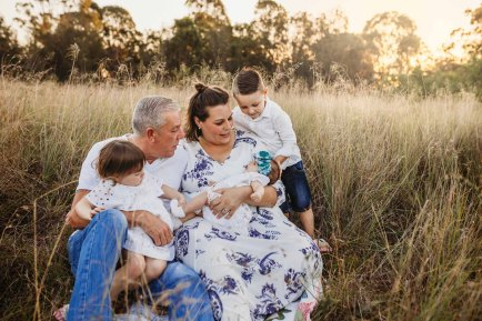 A family sitting in a grass field at sunset