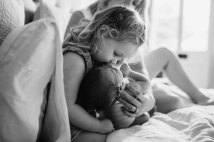 A little girl kisses her newborn brother's head