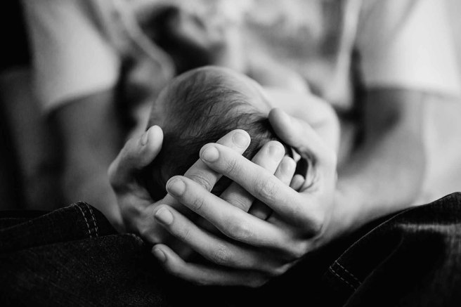 A dad holds his tiny newborn's head in his hands
