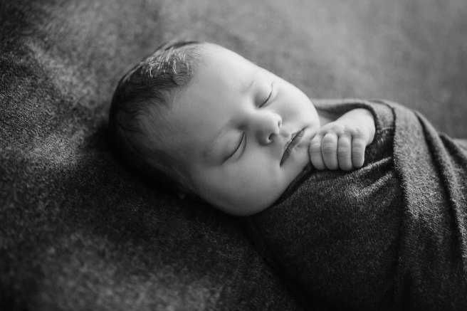 Newborn baby sleeping with little fingers holding a wrap