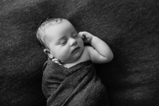 Newborn baby with an arm poking out of her wrap