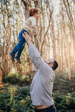 A father hoists his little boy in the air as he soars above his head