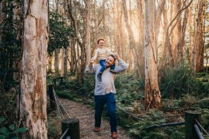 A little boy rides on his dads shoulders running along a path