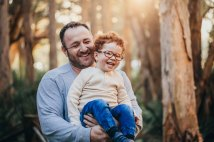 A father and son laugh together during the family photo shoot
