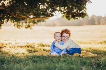 A baby sister and brother cuddle on a blanket under a tree