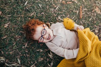 A little boy plays under a blanket in a Sydney park photo shoot
