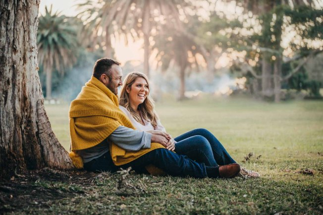 Parents cuddle under a blanket in a Sydney park photo shoot