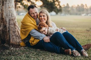 A couple cuddle their son under a blanket in Sydney