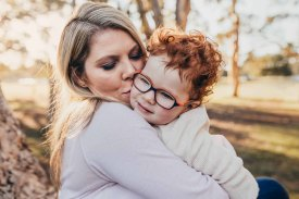 A mum kisses her little boy as the sun sets behind them