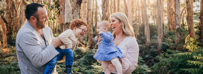 A family of 4 stand in a rainforest lit by a golden sunset