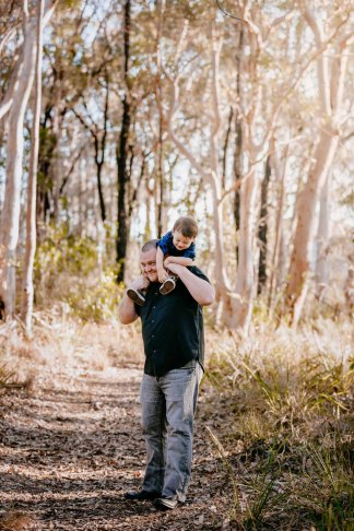 A dad carries his little boy on his shoulders as they giggle together