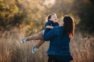 A mum spins her son around during a photo session at sunset