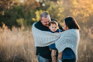 Parents snuggles their son wrapped in a blanket at sunset