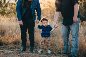 A little boy stands holding his parents hands as the sun sets behind them