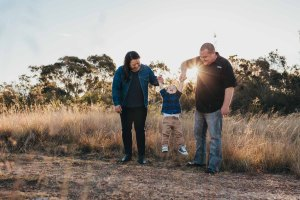 Parents hoist their giggling son into the air as the sun sets behind them
