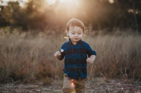A little boy crosses a grass field eating a lollypop as the sun sets behind him