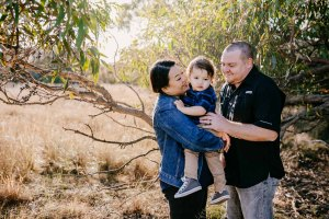 Parents hold their baby boy between them in a grassy field