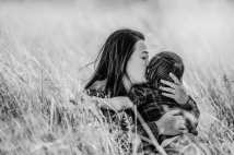 A mother pulls her son close for a kiss on the cheek surrounded by long grass