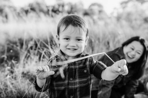 A little boy tries to tickle his photographer with a piece of grass
