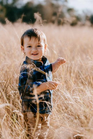 A little boy smiles as long grass tickles his face at sunset