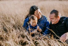 A little family giggle together sitting in long grass at sunset