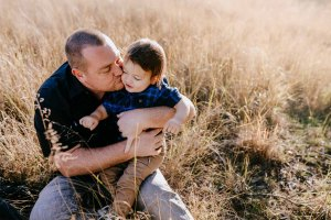 A father kisses his little boy as they sit in long grass at sunset