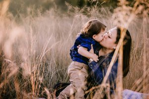 A mother kisses her little boy as they sit in long grass at sunset