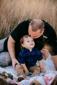 A father snuggles his son in the long grass at sunset