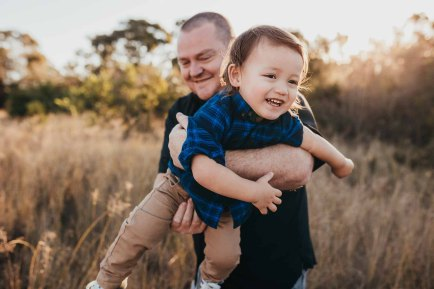 A dad whooshes his son around during their photo session at sunset