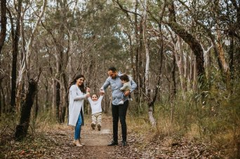 Family with 2 little boys playing on a bush track