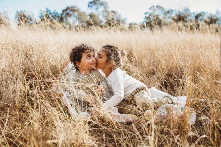 A boy kisses his brothers cheek as they sit in a grass field at sunset