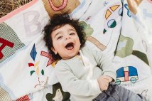 A baby boy giggles and smiles at the camera as he lays back on a rug