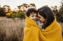 A mother and her baby boy snuggle together wrapped up in a blanket as they smile