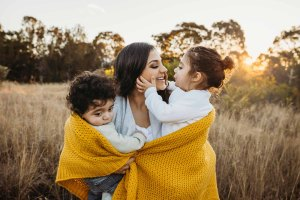 A mother and her baby boys snuggle together wrapped up in a blanket as they smile