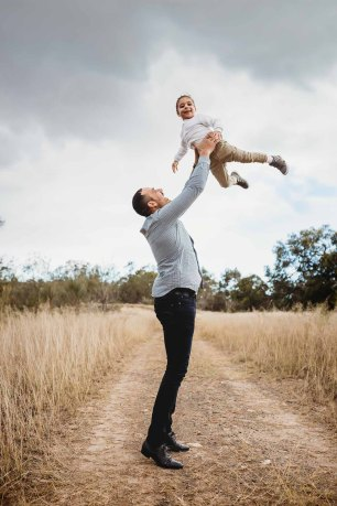 A father swing his son above him as they play aeroplane games