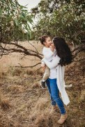 A mother kisses her little boy under a tree in a grassy field