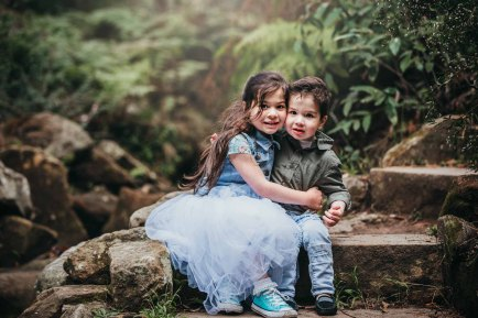 Siblings share a hug as they sit on sandstone steps during their photo session