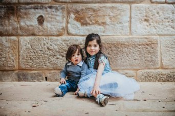 Siblings share a cuddle against the sandstone walls of historic Lennox Bridge