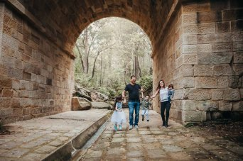 Parents swing their son between them as the walk through historic Lennox Bridge