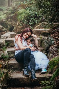 A mother holds her daughter close as they hug on the steps of Lennox Bridge