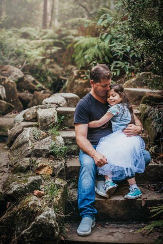 A dad holds his daughter close as they hug on the steps of Lennox Bridge