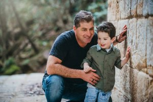 A father hugs his cheeky boy as they stand against a sandstone wall