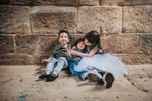Siblings share hugs and kisses as they sit together against a sandstone wall
