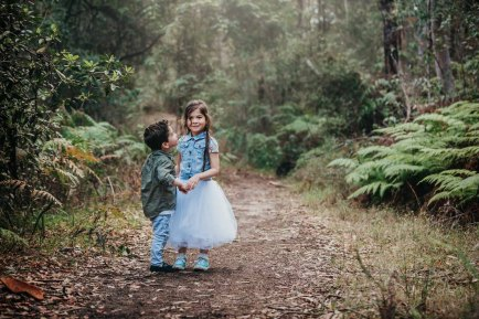 A little boy gazes lovingly at his big sister as the hold hands on a dirt path