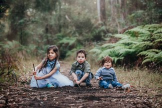 Three siblings sit together along a little dirt path in Glenbrook