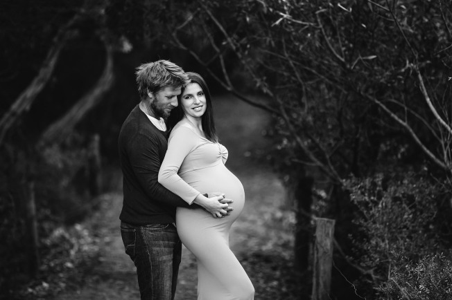 A husband embraces his pregnant wife as they hold her belly