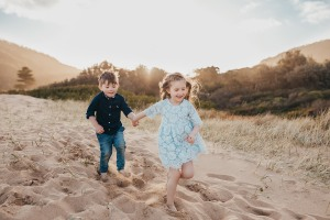 A brother and sister hold hands and race down a sand dune at sunset